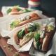 Hotdogs mit Lachs und Meerrettichsoße auf einem Holzbrett